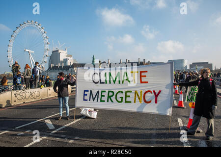 London, UK. 17th November, 2018. Environmental campaigners from Extinction Rebellion block Westminster Bridge, one of five bridges blocked in central London, as part of a Rebellion Day event to highlight 'criminal inaction in the face of climate change catastrophe and ecological collapse' by the UK Government as part of a programme of civil disobedience during which scores of campaigners have been arrested. Credit: Mark Kerrison/Alamy Live News - Stock Photo