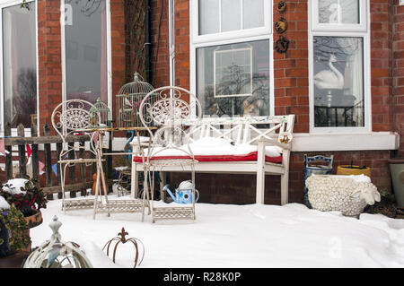 A fantastic view of a funny garden with the bench and the furniture snow covered. - Stock Photo