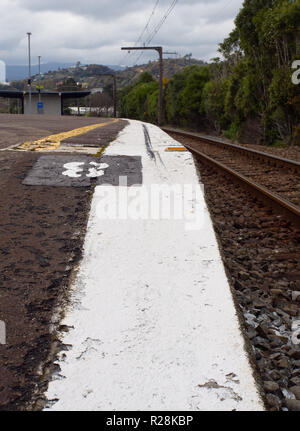 White line on th edge of a train station platform - Stock Photo