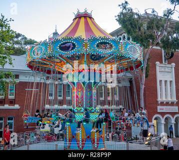 People riding a swing carousel ride Christmas festival Perth Cultural Centre Perth Western Australia. - Stock Photo