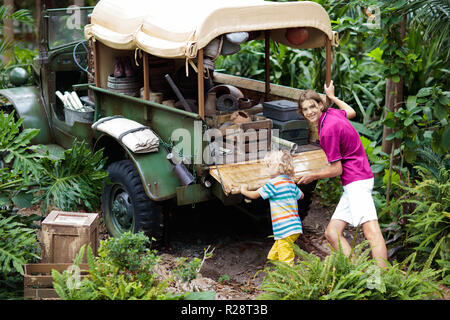 Man and child push car stuck in mud in jungle. Family pushing off road vehicle stuck in muddy dirt terrain in tropical forest. Island adventure drive. - Stock Photo
