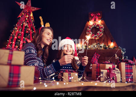 Happy mother in sweater, Christmas deer antlers and little girl in santa helper hat with sparklers in hands, gift boxes on foreground. Having fun over living room, christmas tree, fireplace background - Stock Photo