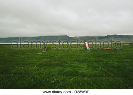 An empty children's playground with a swing, see-saw and slide in the remote empty Iceland landscape. - Stock Photo
