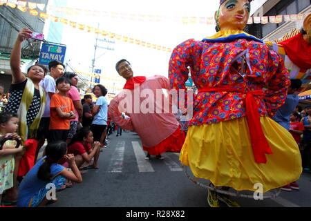 Tourist taking selfie picture during the Higantes (Giant) effigy marches on the streets town of Angono province of Rizal on November 18, 2018. Higantes (Giant) Festival is celebrated November in the city of Angono, Province of Rizal in the Philippines to honor San Clemente, the patron saint of fishermen. The festival features a parade of hundreds of higantes, papier-mâché giants. Higantes (Giant) are puppets rendered as man or woman in various costumes; their face gives a commanding look, their hands on the waist. (Photo by Gregorio B. Dantes Jr./Pacific Press) - Stock Photo