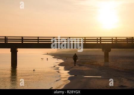 Prerow, Germany - October 10, 2018: Jogging while the sun rises along the Baltic Sea, Germany. - Stock Photo