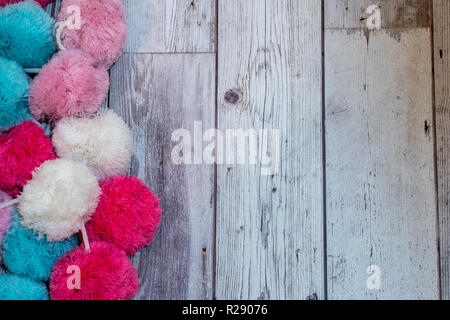 Christmas holiday flatlay with colorful pom pom fabric on wooden background. Colors of blue, pink and white - Stock Photo