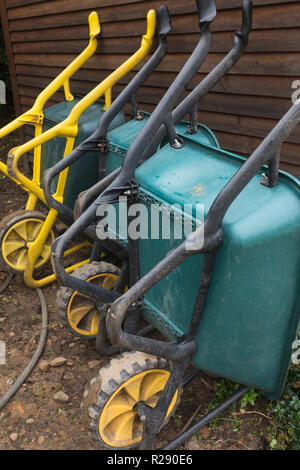 three toughened plastic wheelbarrows lined up and resting or leaning against wooden shed wall in garden area outdoors - Stock Photo