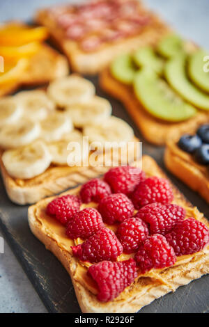 Wholegrain bread slices with peanut butter and various fruits - Stock Photo