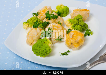 Delicious stewed fish balls with white sauce, steamed broccoli and fresh greens - Stock Photo