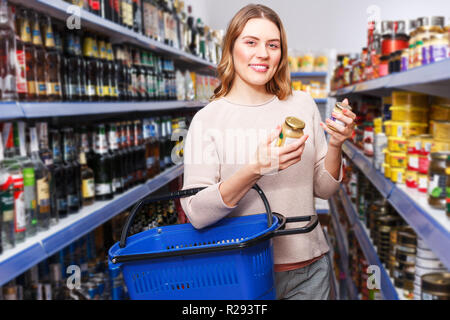 Positive woman with basket in the shop holding preserved jar in grocery section - Stock Photo