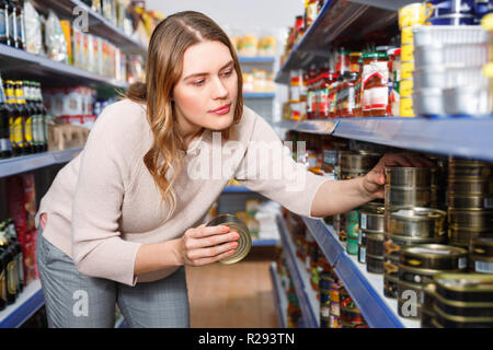 Glad cheerful smiling woman customer holding canned fish  goods in the food store - Stock Photo