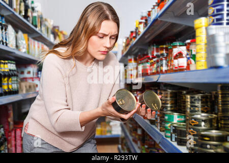 Glad cheerful  woman customer holding canned fish  goods in the food store - Stock Photo