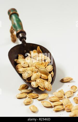 Baked pumpkin seeds in a metal scoop on white background - Stock Photo