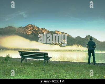 Man stay lonely at the bench in front of the lake. Tourist enjoys beautiful views of mountain lake - Stock Photo