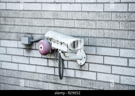 Security closed circuit television (CCTV) camera covered in mold and moss on the bricked wall. - Stock Photo