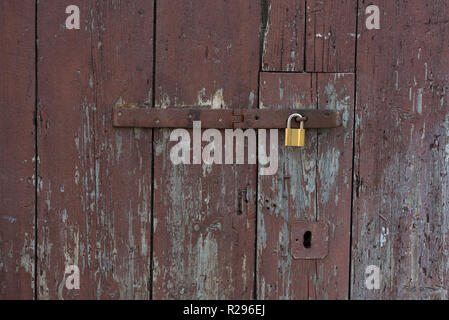 Old wooden doors locked with metal yellow lock. New yellow lock on old brown doors. - Stock Photo