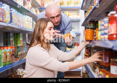 Positive  family couple in the shop holding preserved jar  in grocery section - Stock Photo