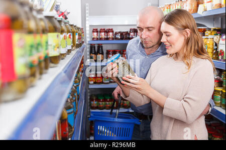 Positive family couple with basket buying canned goods in the food store - Stock Photo
