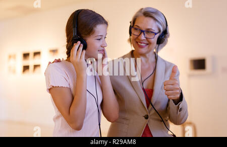 Teenage girl and mature woman using audio guide during excursion in historical museum - Stock Photo