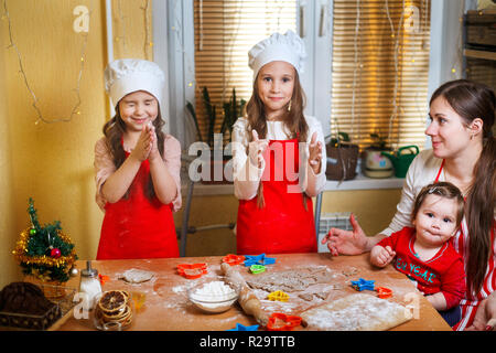 Merry Christmas and Happy Holidays. Family preparation holiday food. Mother and daughters cooking Christmas cookies. - Stock Photo