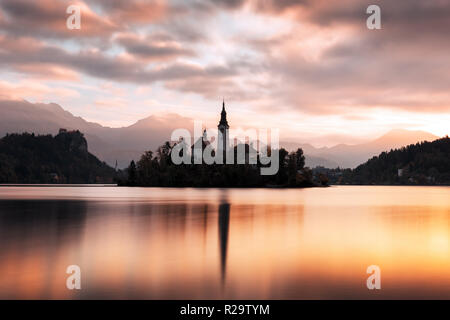 Colorful sunrise view of Bled lake in Julian Alps, Slovenia. Pilgrimage church of the Assumption of Maria on a foreground. Landscape photography - Stock Photo