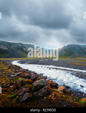 Typical Iceland landscape with river and mountains. Dramatic sky and red stones on a foreground - Stock Photo
