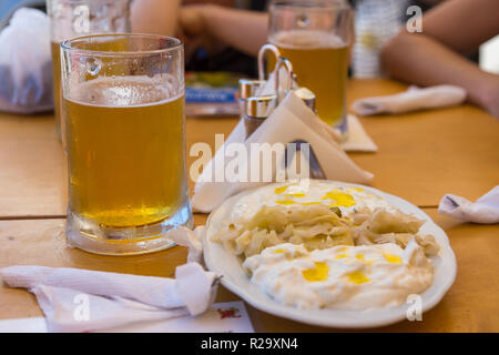 Traditional meal in Albania, cabbage with yoghurt. Beer mug in the background, Tirana, Albania. - Stock Photo