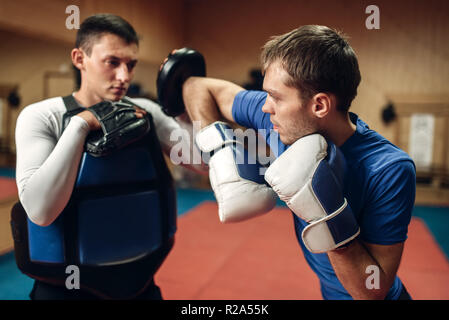 Male kickboxer in gloves practicing elbow kick with a personal trainer in pads, workout in gym. Fighter doing a powerful punch on training, kickboxing - Stock Photo