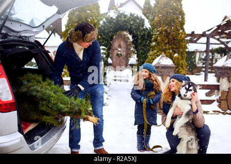 Father brought christmas tree in trunk of SUV car to daughter, mother and dog to decorate home. Family prepares for new year together. Large boot space concept. Snowy winter outdoors - Stock Photo