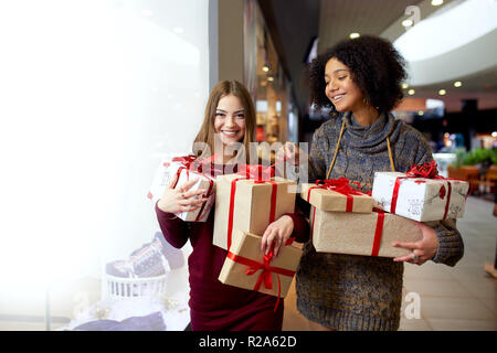 Two mixed race women with gift boxes in hands near storewindow. Multi ethnic girls smiling with presents on christmas new year sale. Caucasian and african american females buy presents for holidays. - Stock Photo