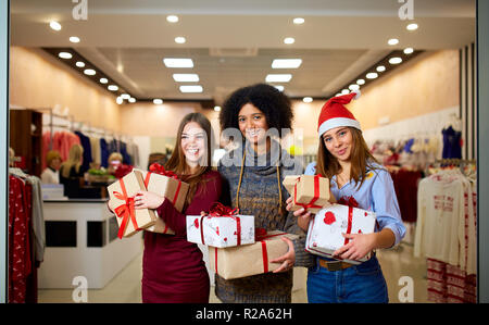 Three mixed race women with gift boxes in hands at store. Multi ethnic girls smiling with presents on christmas new year sale. Caucasian and african american females shopping presents for holidays. - Stock Photo