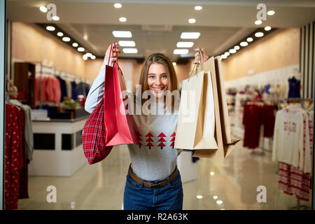 Happy girl shopping gifts in mall on christmas sale. New year holidays shopping idea concept. Smiling woman with colorful paper presents bags wearing christmas hat in store or shop. - Stock Photo