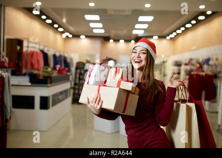 Happy girl shopping gifts in mall on christmas sale. New year holidays shopping idea concept. Smiling woman with colorful paper presents bags and gift boxes wearing christmas hat in store or shop. - Stock Photo