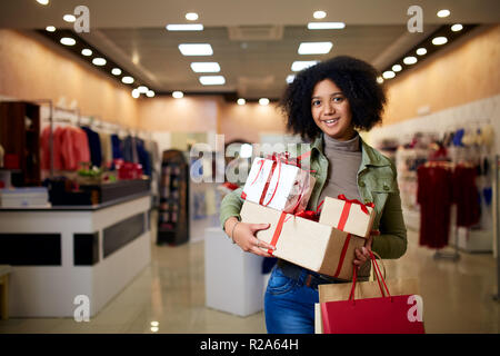 African american girl shopping gifts in mall on christmas sale. New year holidays concept. Smiling attractive mixed racial woman with colorful paper gift boxes wearing christmas hat in store or shop. - Stock Photo