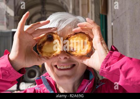 Pasteis de nata, senior woman holding traditional lisbon custard tarts to her face - Stock Photo