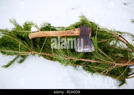Axe on cut down spruce or pine christmas tree branches on snowy ground. Deforestation ban. Irresponsible behavior towards nature, keep green, save forest concept. - Stock Photo