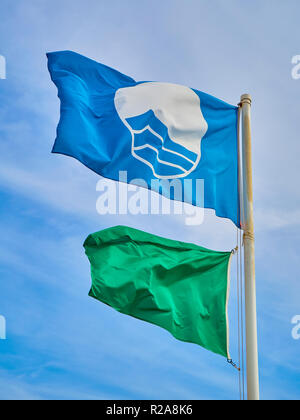 The FEE´s Blue Flag beach and a green lifeguard flag over a blue sky background. - Stock Photo