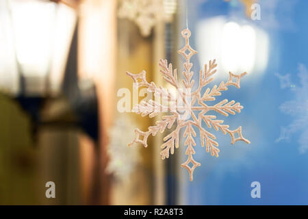 Christmas and new year ornament decoration snowlake handed near window with warm lamp lattern on background. Winter holidays card - Stock Photo