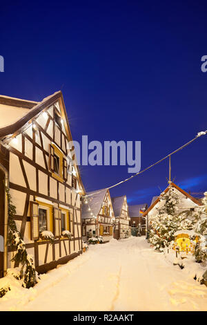 An old village street with half-timbered houses and christmas decoration at night during snowfall in Lachen, Neustadt an der Weinstrasse, Germany. - Stock Photo
