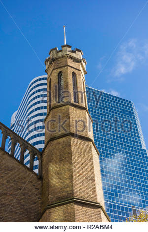 Turret of historic Church of the Holy Trinity Anglican against the modern Eaton Centre in downtown Toronto Ontario Canada - Stock Photo