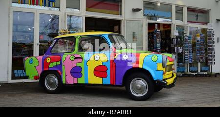 A brightly coloured old Trabant car parked in front of a souvenir shop in the Arkaden shopping centre close to Potsdamerplatz, Berlin, Germany. - Stock Photo