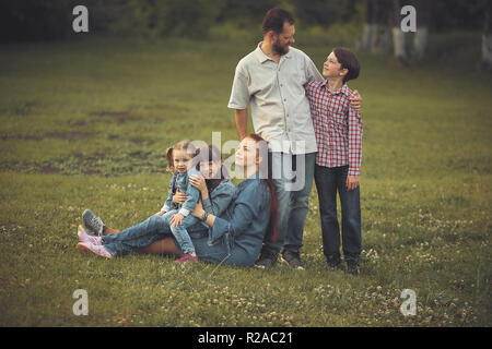 a family of five in the summer in the Park. bearded man and his wife with red hair with three children. happy family. - Stock Photo