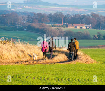 East Lothian, Scotland, United Kingdom, 18th November 2018. UK Weather: A clear sky and sunshine on an Autumn day. A group of walkers and a dog enjoy the hilltop view over an agricultural landscape - Stock Photo
