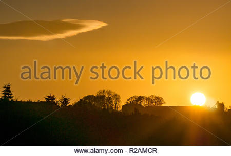 East Lothian, Scotland, United Kingdom, 18th November 2018. UK Weather: A clear sky with sunshine and the last rays of the sun as it sets over the Garleton Hills ridge create an orange glow with a single lenticular cloud and a bird silhouetted in the sky - Stock Photo