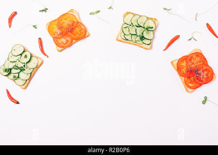 Flat lay frame of sprouts, small peppers and vegetable sandwiches in form of arc with empty space below. Toasts with red tomatoes and green cucumbers  - Stock Photo
