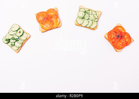 Flat lay frame of vegetable sandwiches in form of arc with empty space below. Toasts with tomatoes and cucumbers on white background, top view. - Stock Photo