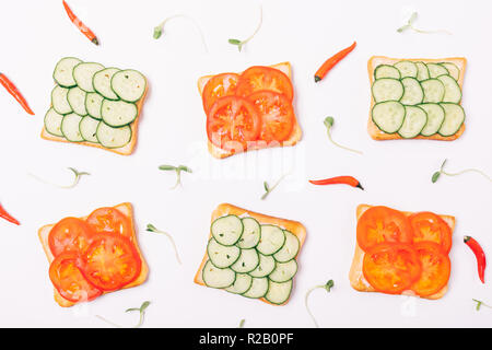 Flat lay arrangement of toasts with slices of fresh green cucumbers and red tomatoes decorated sprouts of herbs and small chili peppers, top view on w - Stock Photo