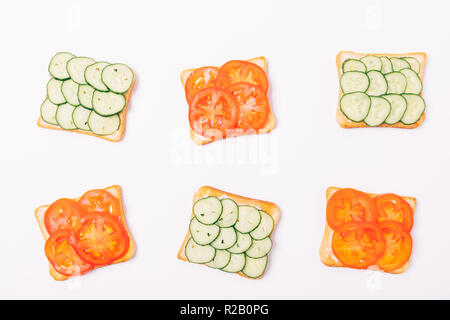 Top view composition of toasts with slices of fresh green cucumbers and red tomatoes, flat lay on white background. - Stock Photo