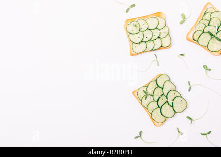 Flat lay decorative side frame of toasts with fresh cucumbers and green seed sprouts on white background, top view with copy space. - Stock Photo