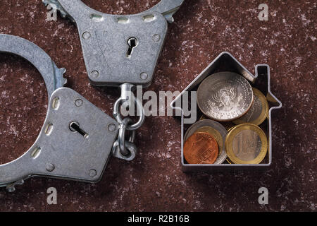 Financial transactions in the real estate market. Handcuffs and various coins on the stone surface